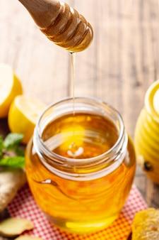 Honig tropft vom schöpflöffel im glas