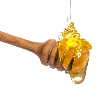 Honig tropft von einem hölzernen honigschöpflöffel lokalisiert auf weißem hintergrund