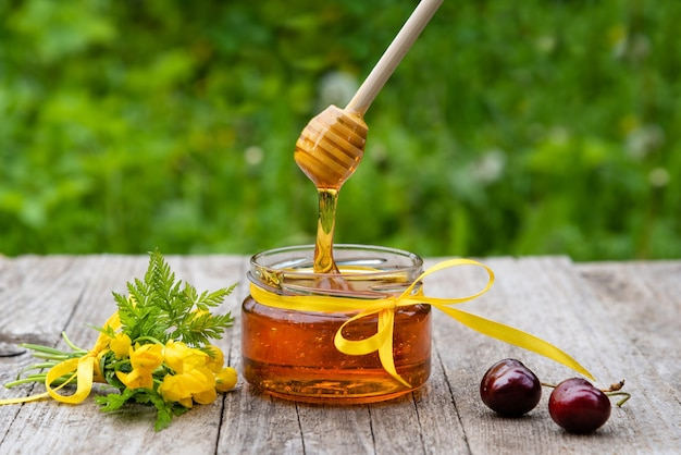 Honig tropft von einem löffel in eine glasschale.