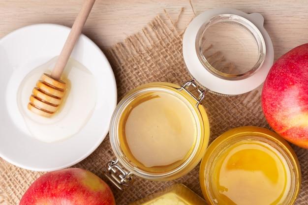 Honig und äpfel auf holztisch.