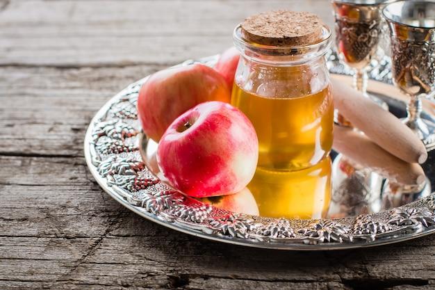 Honig und äpfel auf schönem behälter auf holztischhintergrund. jüdischer feiertag rosh hashanah concept