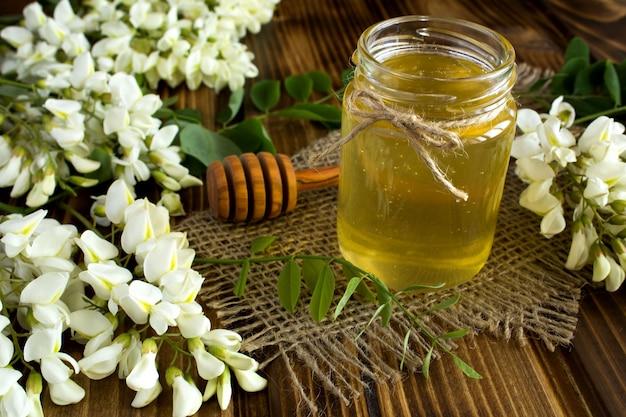 Honig und akazienblumen auf dem rustikalen hölzernen hintergrund