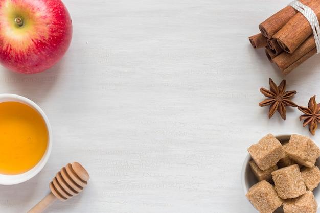 Honig und apfel, brauner zucker und anis mit zimt auf hellem hintergrund