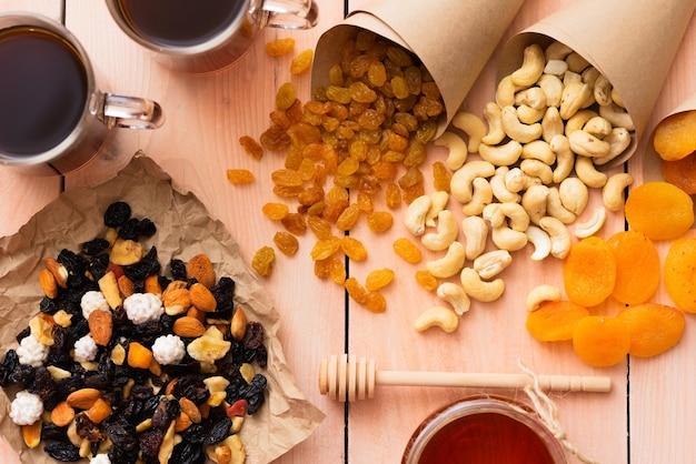 Honig und getrocknete früchte auf einem holztisch.