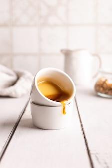 Honig wird aus einer kleinen tasse gegossen
