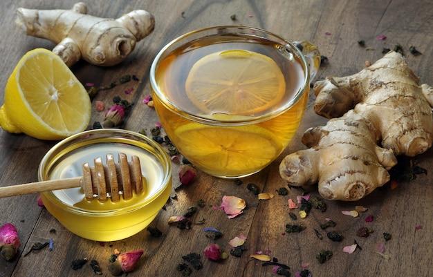 Honig, zitrone, ingwer und eine tasse tee mit zitrone auf einem holztisch. traditionelle erkältungsmittel