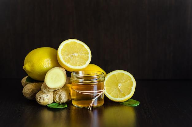 Honig, zitrone, ingwer zur stärkung der immunität gegen erkältungen, grippe, epidemie auf dunklem holz mit kopierraum, weichzeichner