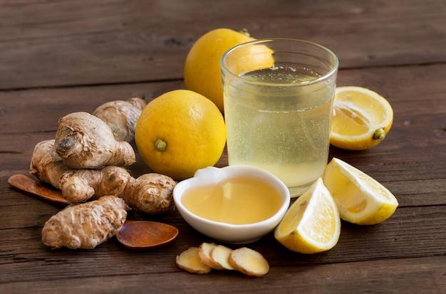 Honig-, zitronen- und ingwer-tonikum auf einer hölzernen tablettennahaufnahme