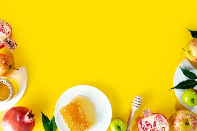 Honigapfel und granatapfel auf einem gelben hintergrundkonzept jüdisches neues jahr frohe feiertage rosh