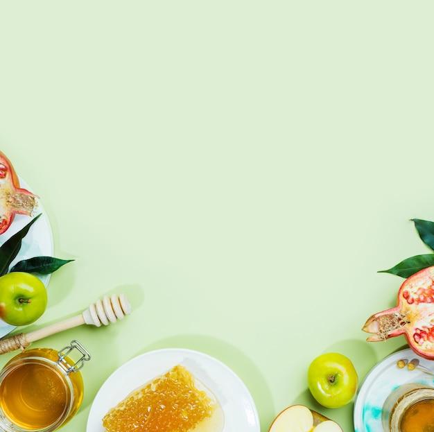 Honigapfel und granatapfel auf einem mintgrünen hintergrundkonzept jüdisches neues jahr frohe feiertage rosh