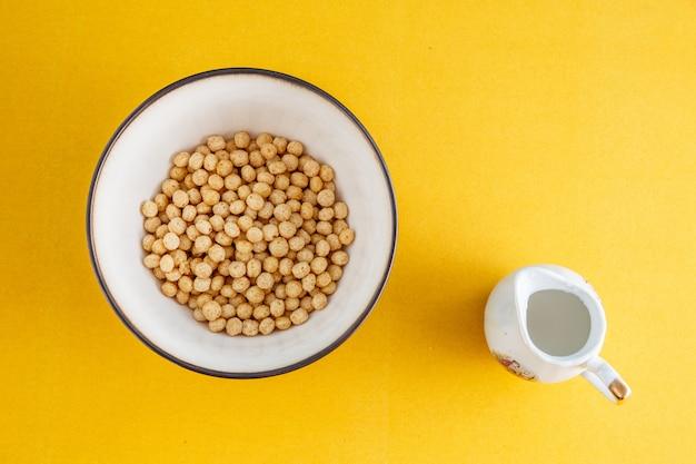 Honigbälle von verschiedenen getreide in einer tiefen schüssel und milch auf gelb