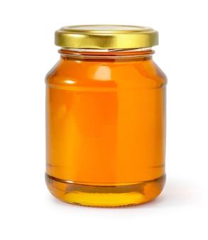 Honigglas auf weißem hintergrund mit beschneidungspfad isoliert
