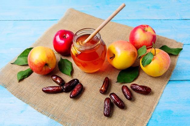 Honigglas, datteln und äpfel auf leinwandserviette