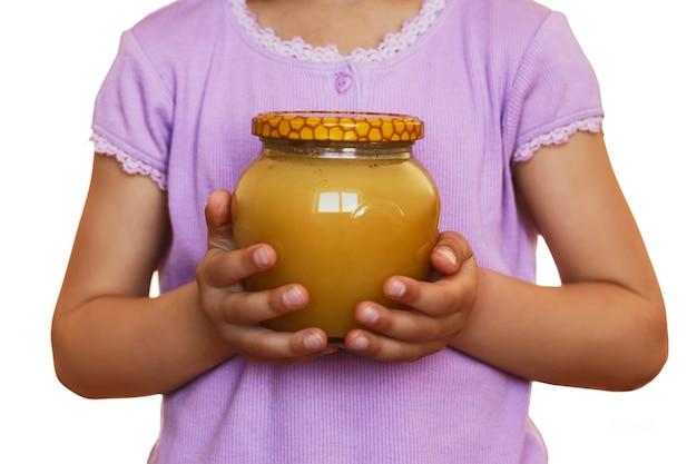 Honigglas in kinderhänden kind hält glas voller honig auf weißem hintergrund