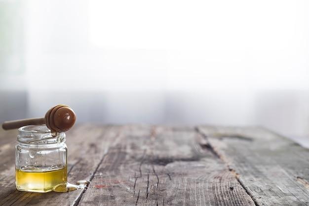 Honigglas mit einem hölzernen stock lässt honig auf einem alten hölzernen hintergrund über hellem fenster ab