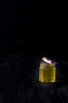 Honigglas mit einem hölzernen stock lässt honig auf einem dunklen hintergrund ab