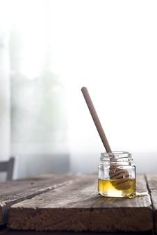 Honigglas mit einem holzstab auf einem alten hölzernen hintergrund über hellem fenster,