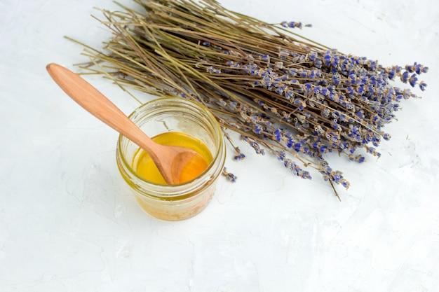 Honigglas und trockener lavendel blüht auf einem weißen schäbigen konkreten hintergrund