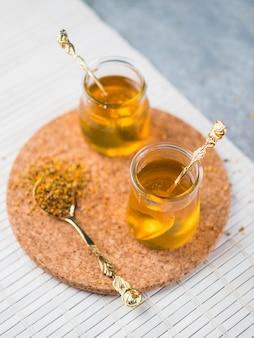 Honigglastöpfe mit löffel- und bienenpollen auf korkenuntersetzern