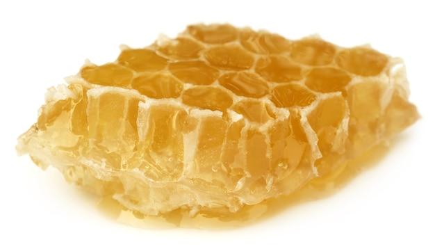 Honigkamm mit honig auf weißem hintergrund