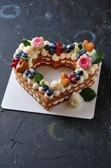 Honigkuchen mit frischen blaubeeren, kräutern und frischkäsecreme. dessert für einen geliebten menschen. herzkuchen.
