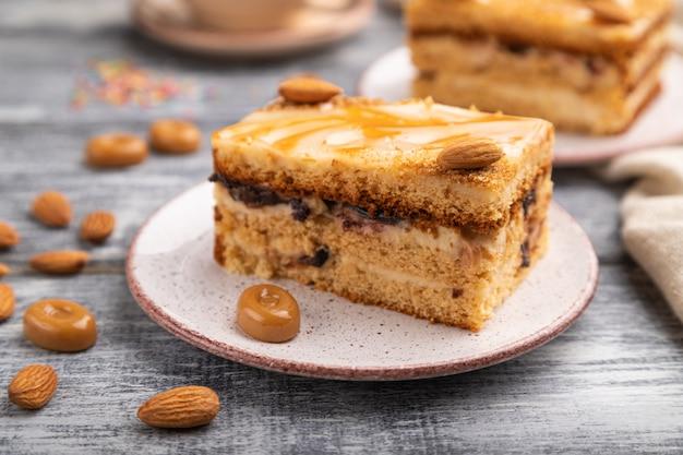 Honigkuchen mit milchcreme, karamell, mandeln und einer tasse kaffee auf einem grauen hölzernen hintergrund. seitenansicht, selektiver fokus.