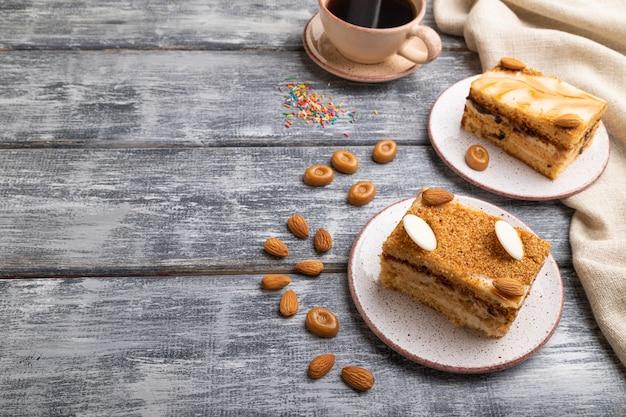 Honigkuchen mit milchcreme, karamell, mandeln und einer tasse kaffee auf einem grauen hölzernen hintergrund. seitenansicht,