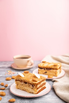 Honigkuchen mit milchcreme, karamell, mandeln und einer tasse kaffee auf einem grauen und rosa hintergrund. seitenansicht, selektiver fokus,
