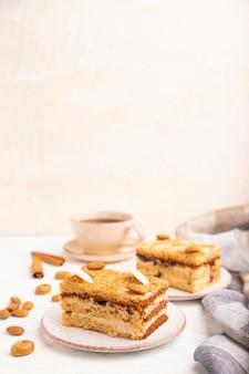 Honigkuchen mit milchcreme, karamell, mandeln und einer tasse kaffee auf einem weißen betonhintergrund. seitenansicht, kopierraum, selektiver fokus.