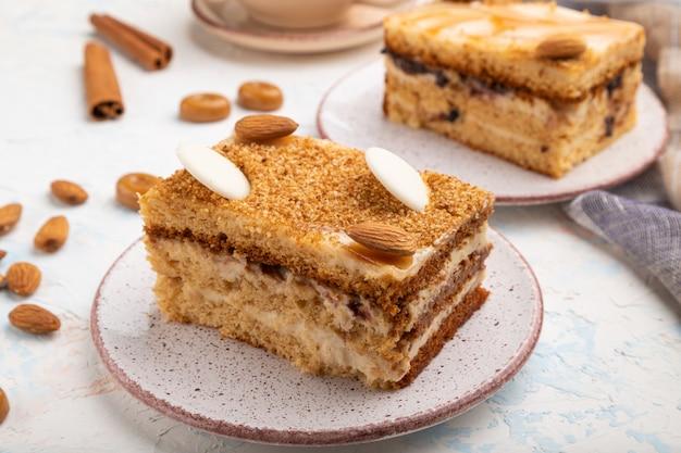 Honigkuchen mit milchcreme, karamell, mandeln und einer tasse kaffee auf einem weißen betonhintergrund. seitenansicht, nahaufnahme.