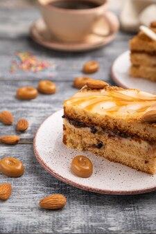 Honigkuchen mit milchcreme, karamell, mandeln und einer tasse kaffee auf grauer holzoberfläche und leinentextil