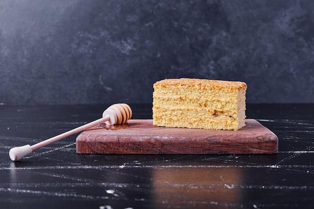 Honigkuchen mit zimt und früchten auf weißem teller neben tee.