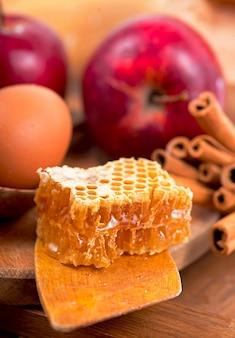 Honiglöffel, glas honig, äpfel und zimt auf holzhintergrund im rustikalen stil.