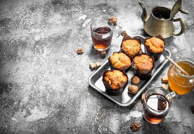 Honigmuffins mit duftendem tee. auf einem rustikalen tisch.