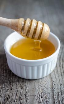 Honigschale mit schöpflöffel und fließendem honig