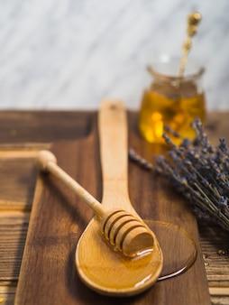 Honigschöpflöffel auf hölzernem löffel über dem hackenden brett