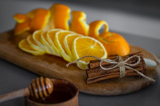 Honigschöpflöffel der zimtstangen, orange scheiben und schale auf hölzernem brett. gewürze und zutaten