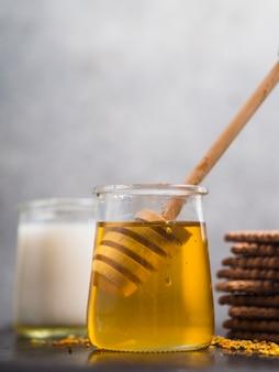Honigschöpflöffel im honigtopf mit keksen gegen grauen hintergrund