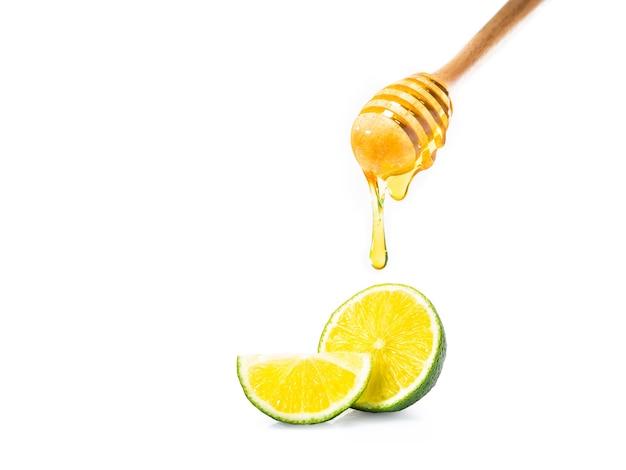 Honigschöpflöffel mit dem honig, der unten tropft und schnitt frischen kalk auf weißem hintergrund