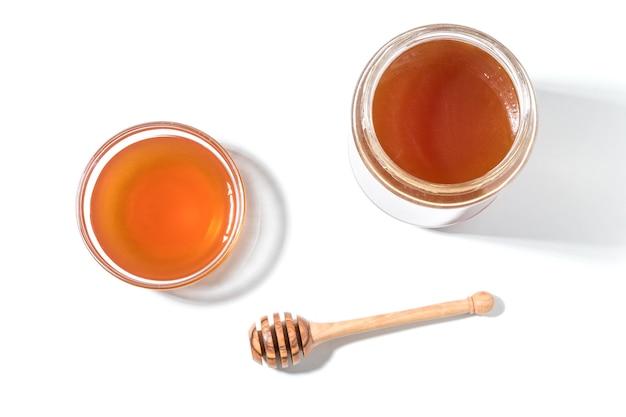 Honigschöpflöffel und honig im glas auf weißer oberfläche.