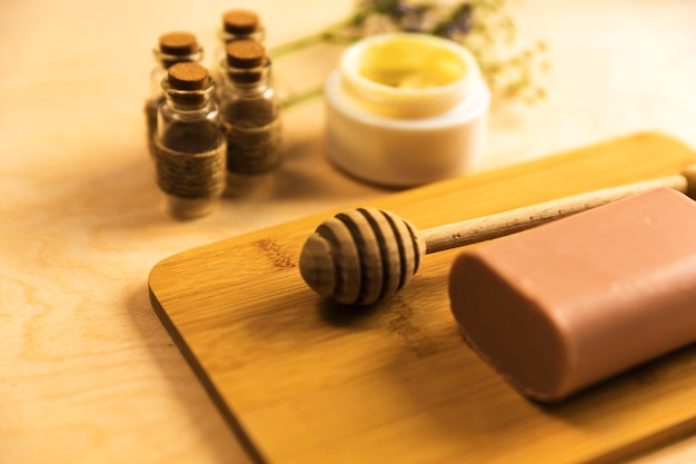 Honigschöpflöffel und -seife auf hölzernem brett mit aromaölen und feuchtigkeitscreme