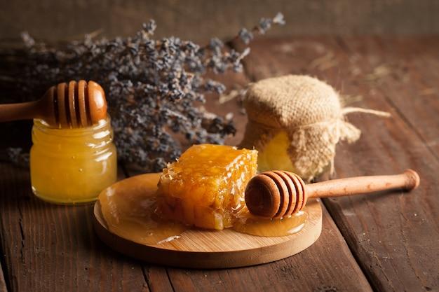 Honigschöpflöffel und wabe. nüsse und äpfel mit honig und nüssen verschiedener art