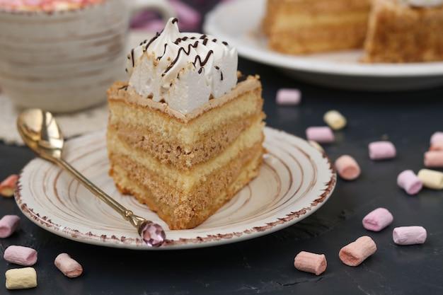 Honigschwammkuchen mit der buttercreme gelegen auf einem dunklen hintergrund
