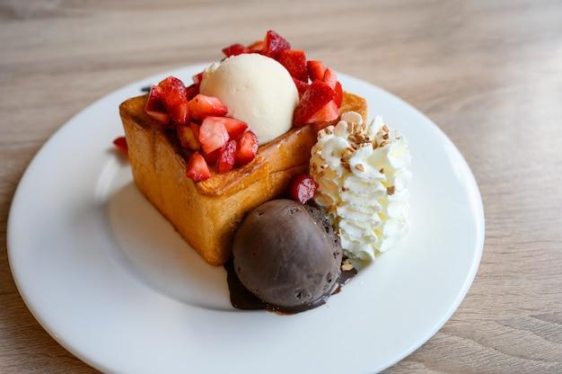 Honigtoast mit geschnittenen erdbeeren, vanille, dunklem schokoladeneis und schlagsahne in weißem teller