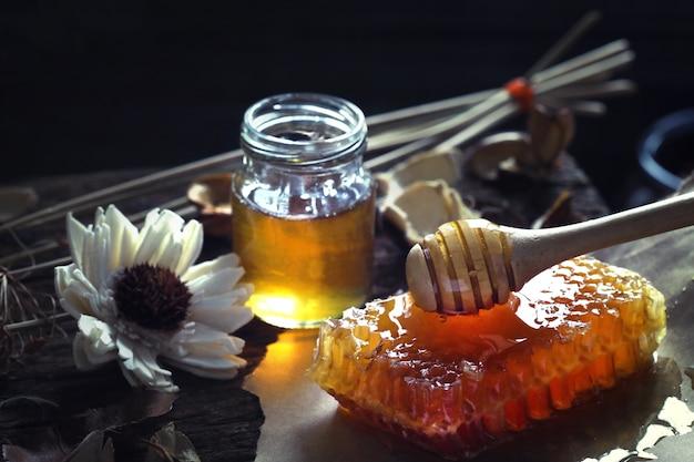 Honigtöpfe mit waben auf einem holztisch mit blumen