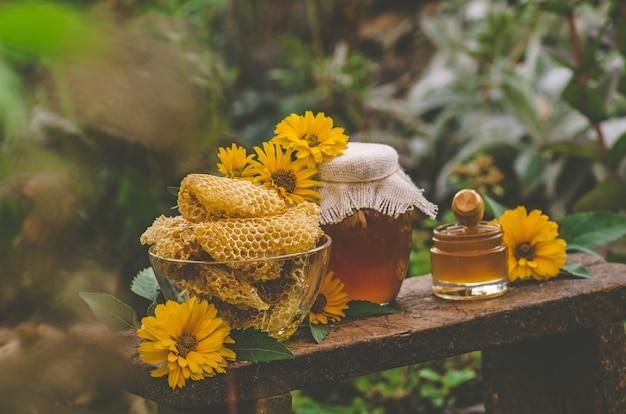 Honigtopf, schöpflöffel, glas frischer honig, bienenwabe auf einem holztisch draußen. honig mit honigschöpflöffel auf holztisch