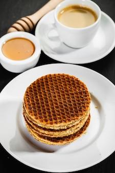Honigwaffeln und kaffee auf keramik