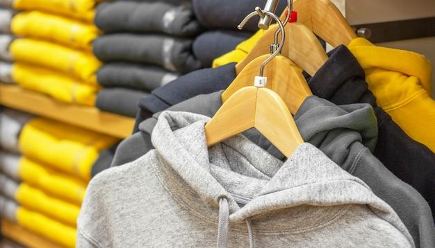 Hoodie hängen an kleiderbügeln trendige farbe des jahres 2021 gelb und grau