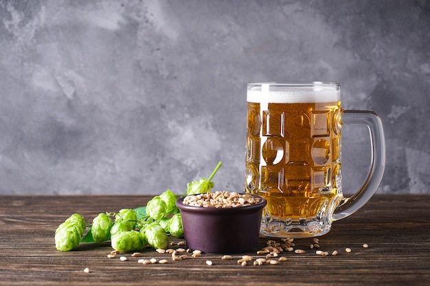 Hopfen und ein glas helles bier auf holzfläche, platz für text.