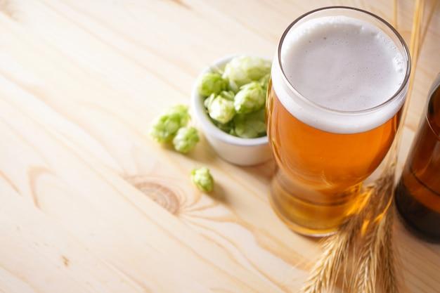 Hopfen und helles bier auf holzfläche, platz für text